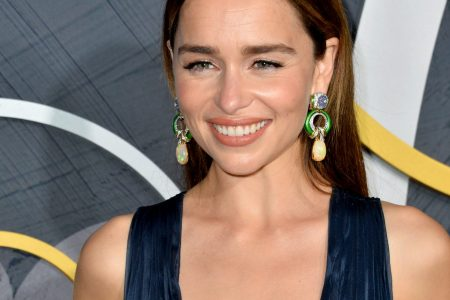 Emilia Clarke smiles at a red carpet event wearing a deep V dress and statement earrings. She has long brown hair that is parted in the middle and sits behind her shoulders.