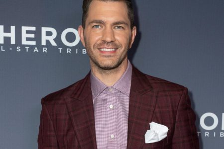 Andy Grammer smiles at a red carpet event. he wears a deep burgundy suit jacket.