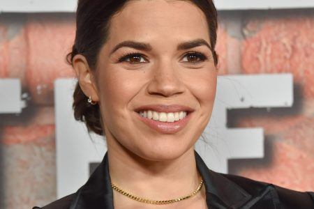 America Ferrera smiles at a red carpet event. Her dark hair is tied back and she wears a black suit jacket.