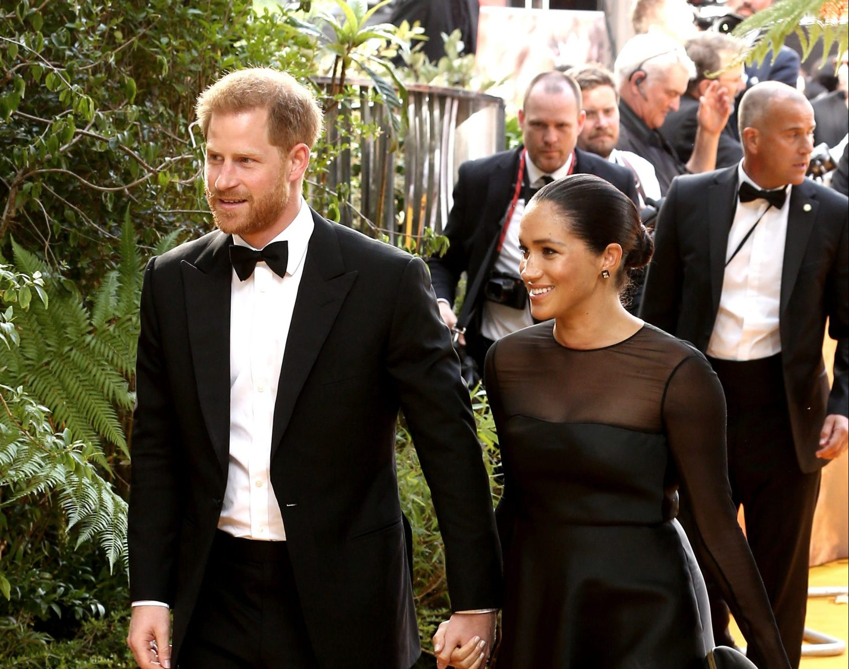 Prince Harry and Duchess Meghan attend a red carpet event, smiling. He wears a tuxedo and she wears a black dress with a sheer neckline and sleeves.