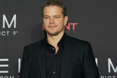 Matt Damon smiles on the red carpet dressed in a black shirt and suit jacket.