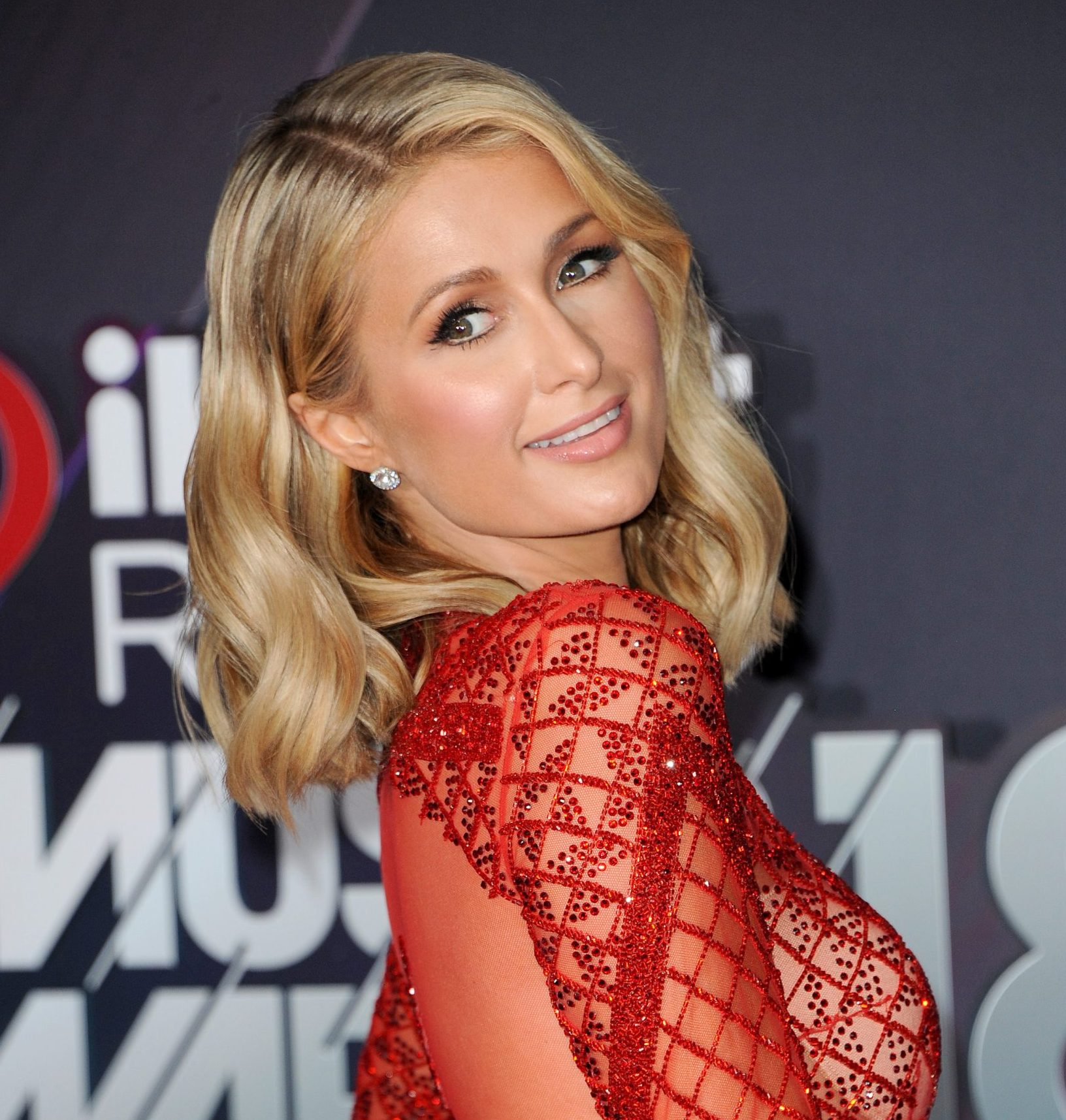 Paris Hilton wears a striking red dress at a red carpet event. She is looking over her shoulder at the camera and her hair is just below her shoulders.