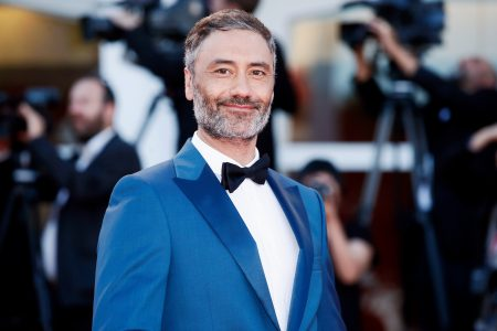 Taika Waititi wears a blue tux and black bow tie at a red carpet event. He has some greying facial hair and is smiling at the camera. Behind him is a blur of paparazzi.