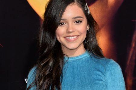 Jenna Ortega smiles at a red carpet event. She has long dark brown hair and wears a blue dress.