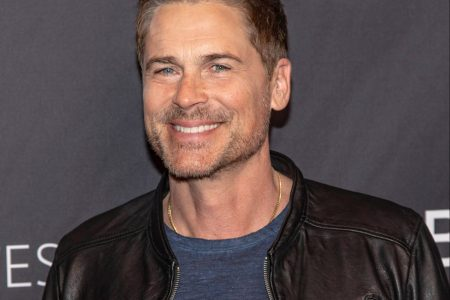 Rob Lowe smiles at a red carpet event. He's wearing a leather jacket.
