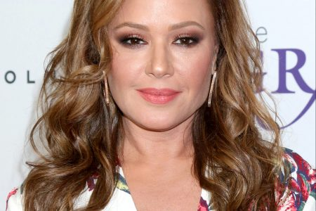 Leah Remini attends a red carpet event. She has wavy brown hair and wears a floral white and pink top.