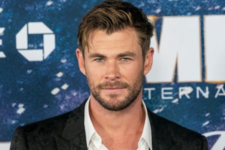 Chris Hemsworth smiles at a red carpet event. He wears a black suit and a white shirt.