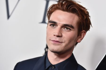 KJ Apa smiles at a red carpet event. He has dark red hair and wears a black jacket and shirt.