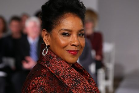 Phylicia Rashad wears a red coat on a runway and smiles at the camera.