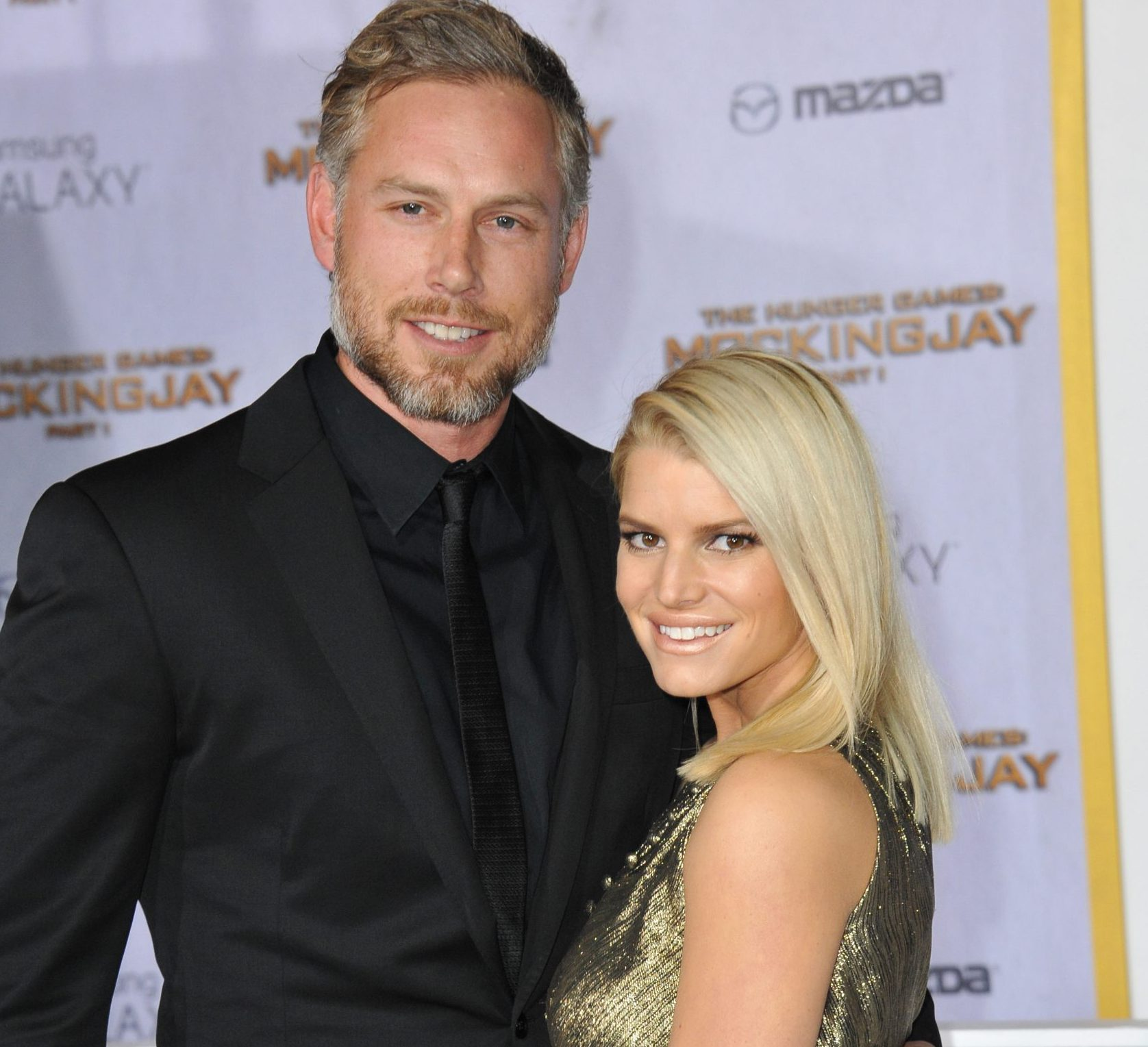 Eric Johnson and Jessica Simpson smile at a red carpet event. He is tall and wears a black suit. She wears a sleeveless gold dress and has straight blonde hair that sits just past her shoulders.