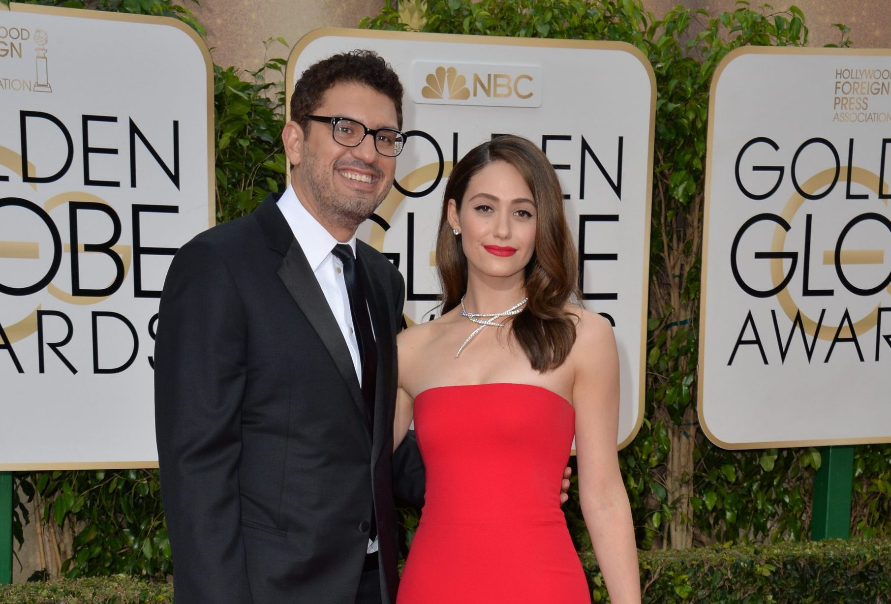 Sam Esmail and Emmy Rossum smile at a red carpet event. Emmy is wearing a stunning strapless red dress and wears matching red lipstick.