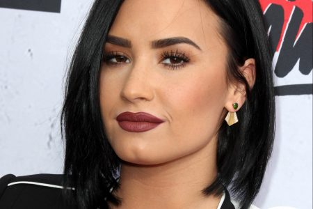 Demi Lovato at a red carpet event. She has a sleep black bob and wears a black and white jacket.