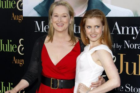Meryl Streep and Amy Adams smiling at a red carpet event. Meryl wears a red dress with black cardigan and belt. Amy Adam wears a sleeveless white dress.