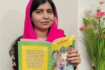 """Malala wears a pink scarf and holds up a copy of her """"assembly"""" magazine."""