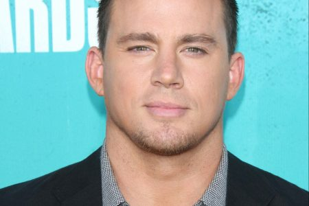 Channing Tatum on the red carpet at a press event. He wears a dark suit jacket and shirt with his top buttons undone.