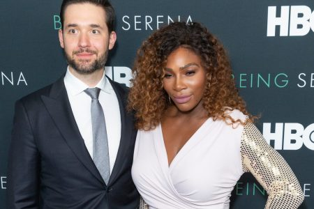 Alexis Ohanian and Serena Williams at a red carpet event. He wears a suit and tie and she wears a shimmery white dress.