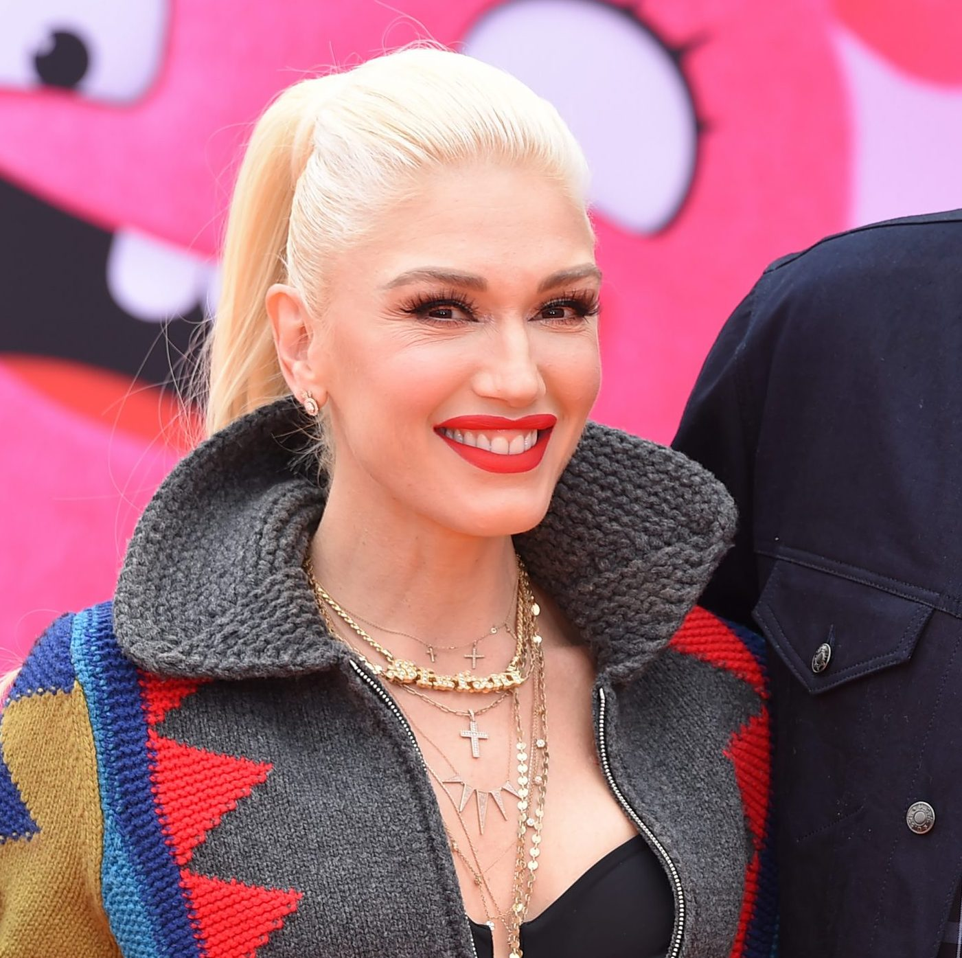 Gwen Stefani smiles at a red carpet event. She has platinum blonde hair thats tied back in a pony tail. She wears bright red lipstick.