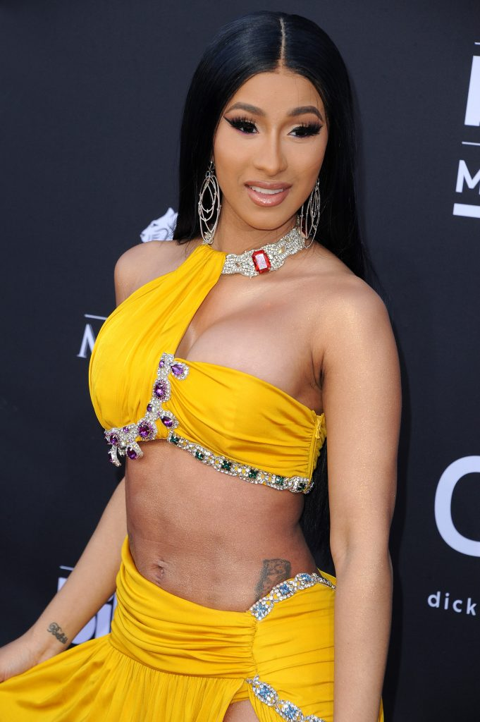 Cardi B wears a two-piece yellow dress at a red carpet event. She has long black hair and she's smiling.
