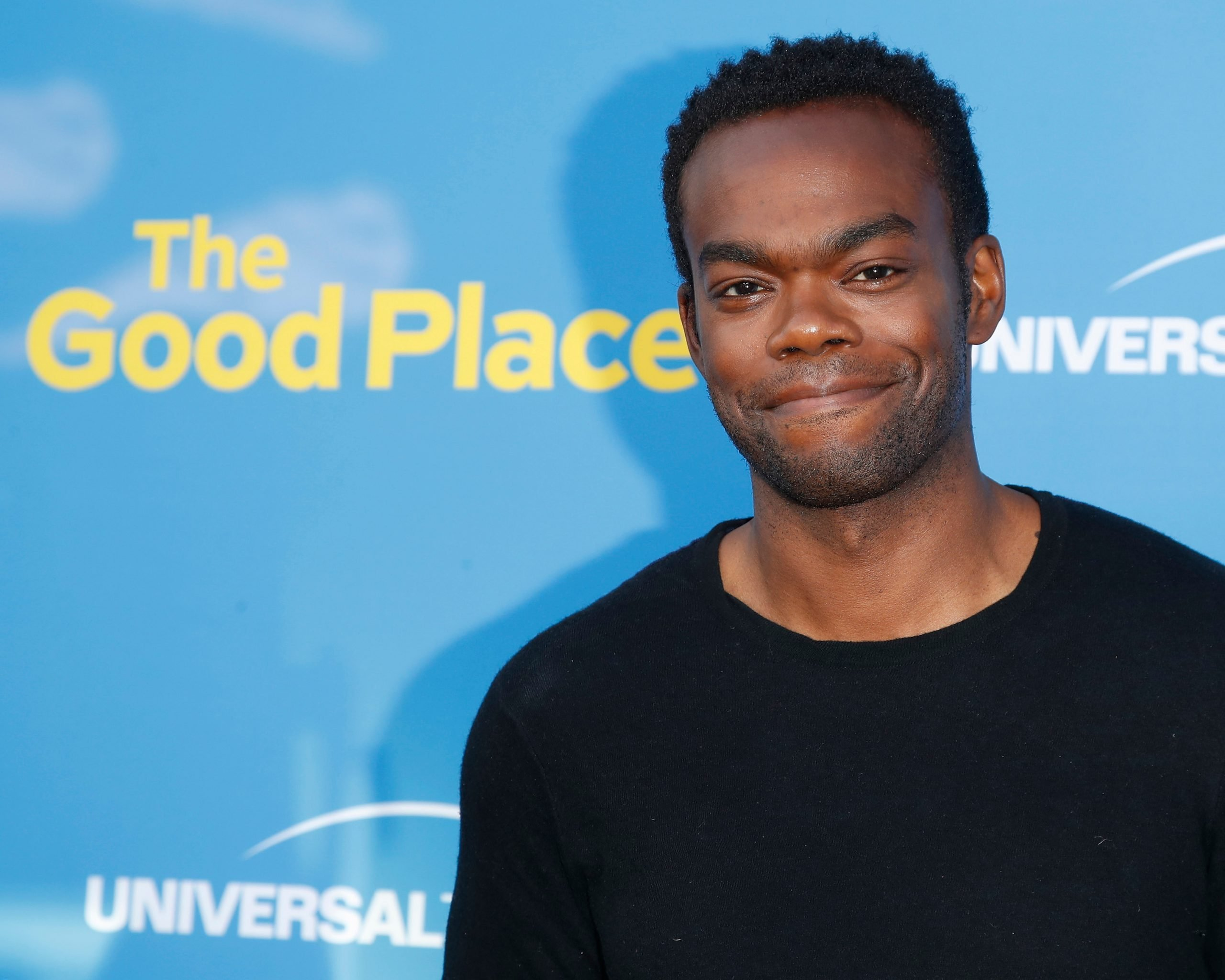 William Jackson Harper smiles at a red carpet event. He is a black man and wears a black top.