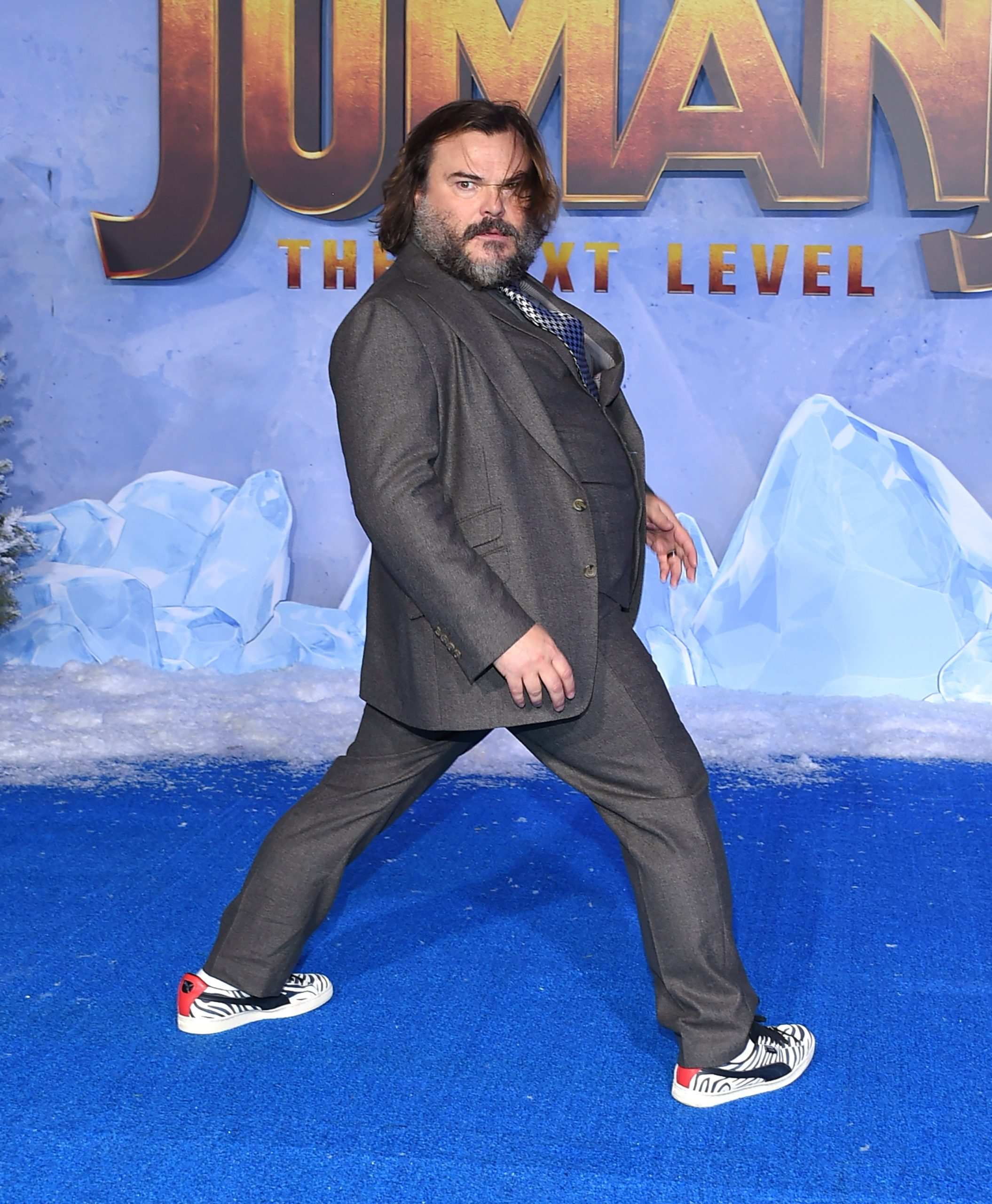 Jack Black at a red carpet event. He wears a grey suit and the carpet is blue!