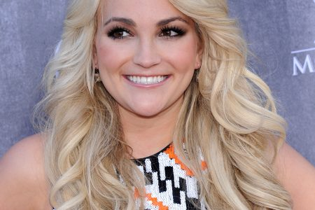 Jamie Lynn Spears smiles at an outdoor press event. She has long blonde layered hair and she is looking off to the left of the camera.