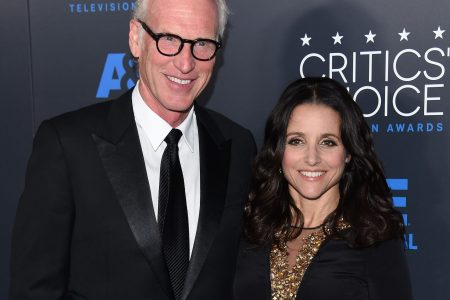 Brad Hall and Julia Louis-Dreyfus smile at a red carpet event.