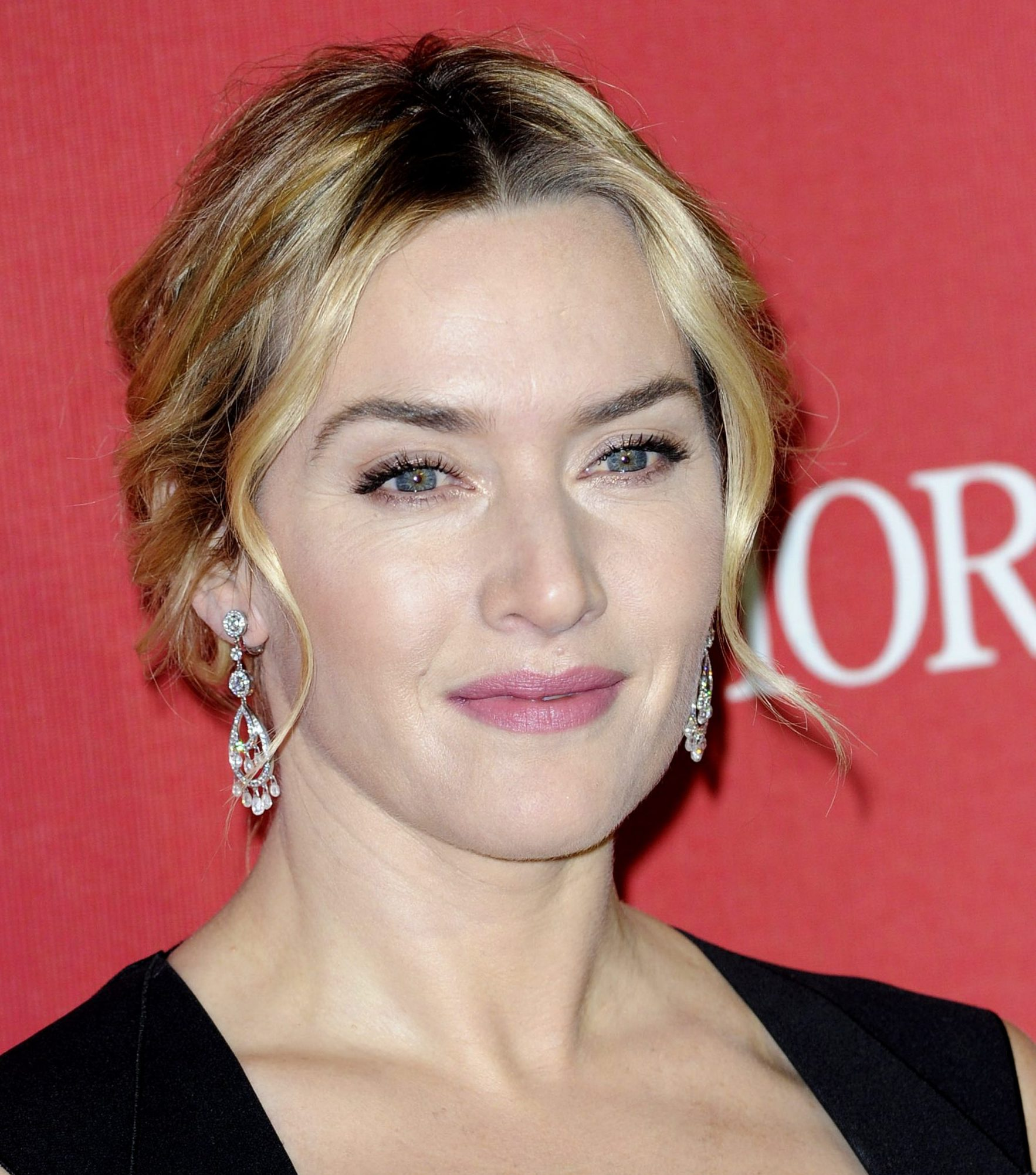 Kate Winslet smiles at a red carpet event. Her blonde hair is elegantly tied back with a few wavy strands falling around her face. She wears dangling crystal earrings and a black dress.