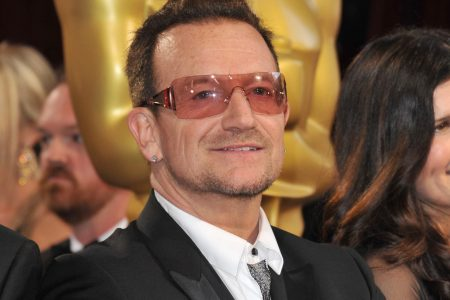 Bono at a red carpet event wearing rose tinted sunglasses and a suit
