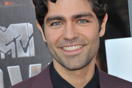Adrian Grenier smiles at a red carpet event. He's wearing a burgundy suit jacket with a black shirt and tie. He has curly dark hair and piercing blue eyes.