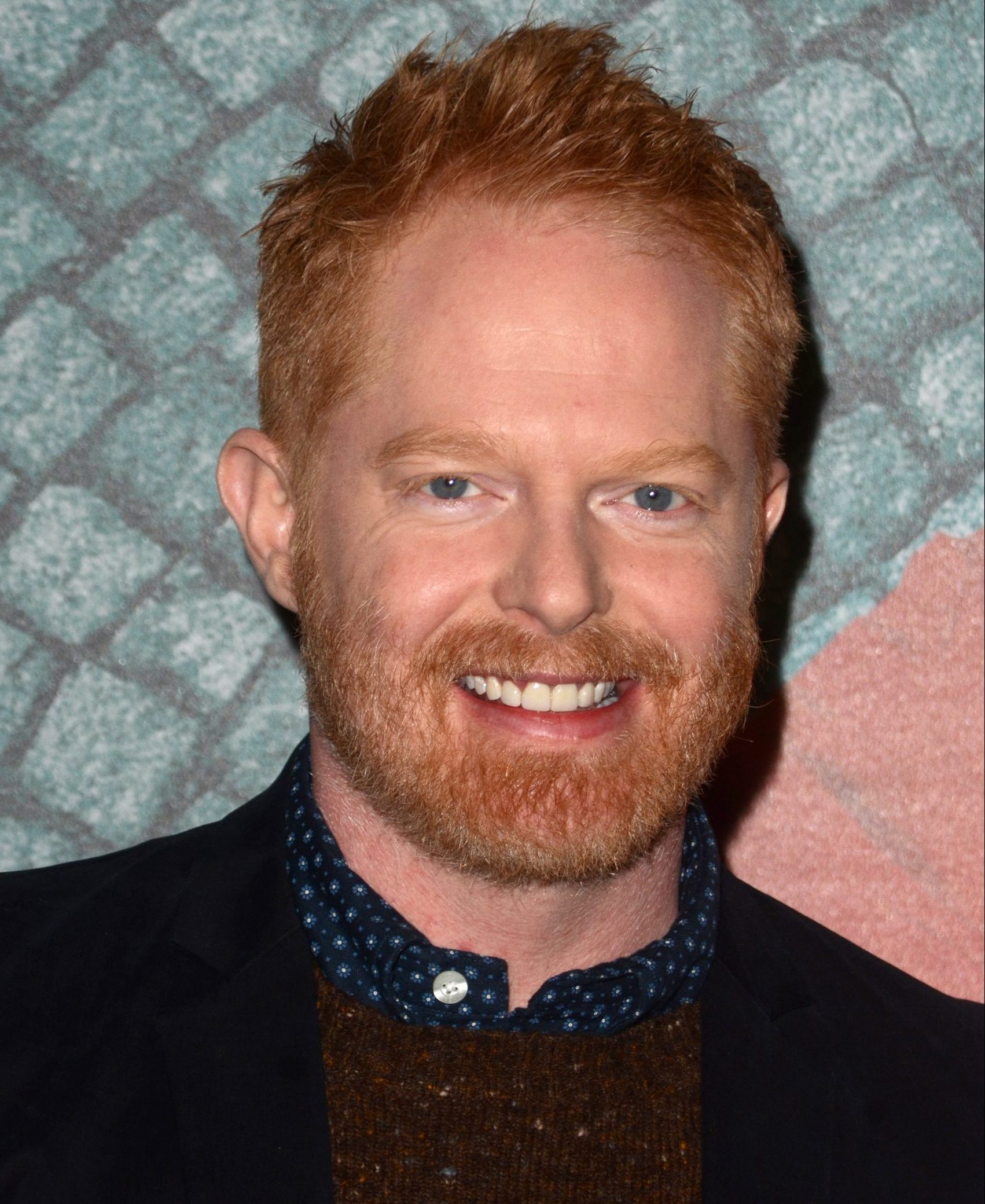 Jesse Tyler Ferguson wears a black shirt and has red hair and facial hair. He's smiling at a red carpet event.