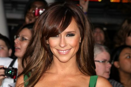 Jennifer Love Hewitt smiles at a red carpet event. She's wearing a dark satin green dress and has long brown hair with a side swept fringe. She's smiling.