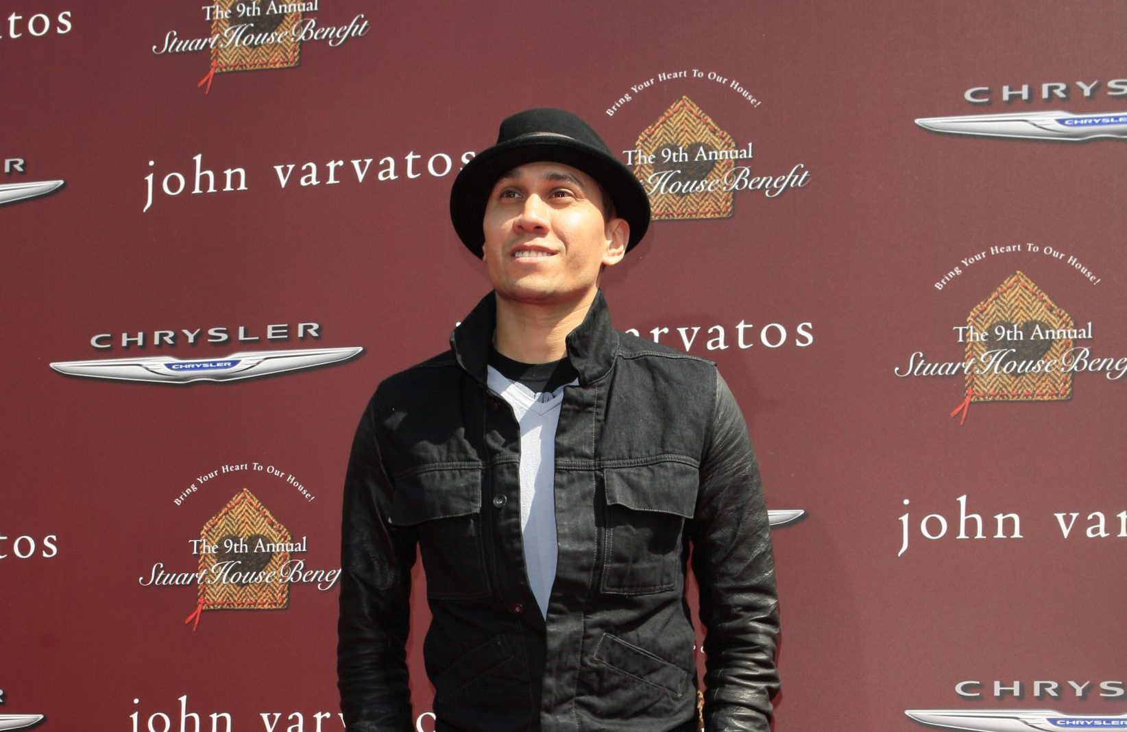 Taboo from the Black Eyed Peas looking up at the sky at an outdoor press event.He's dressed in black and wears a black hat.