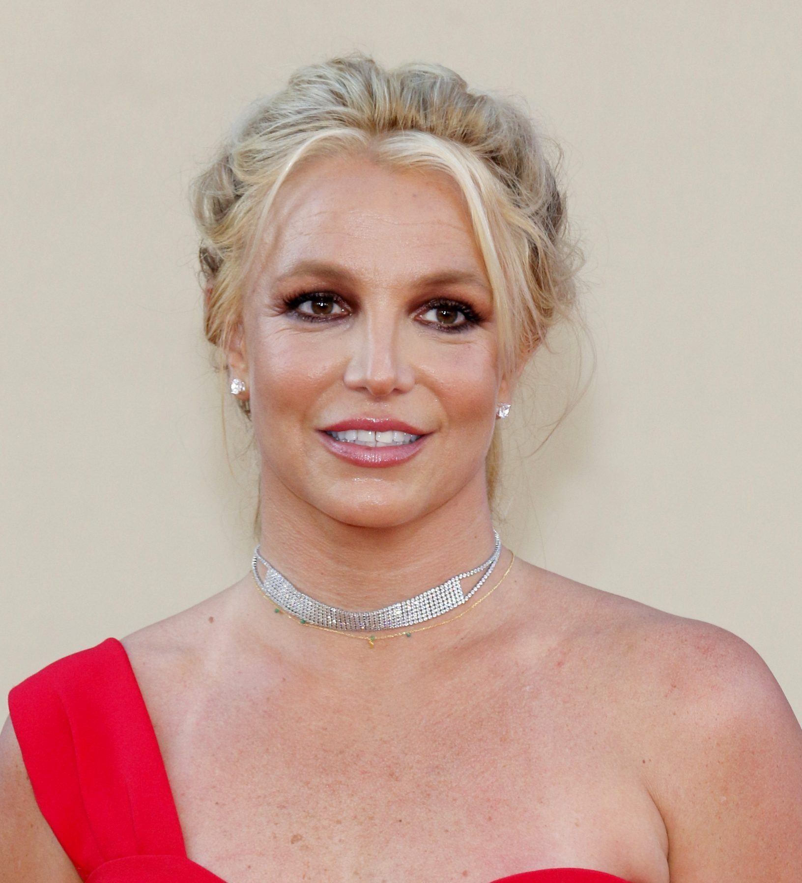 Britney Spears attends an outdoor event. She wears a one shoulder red dress and has her blonde hair styled up.