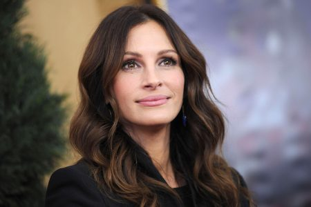 Julia Roberts poses at an outdoor press event. She has wavy brown hair and is looking up at the sky.