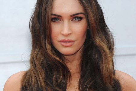 Megan Fox at a red carpet event. She has long brown hair that sits in waves over her shoulders.