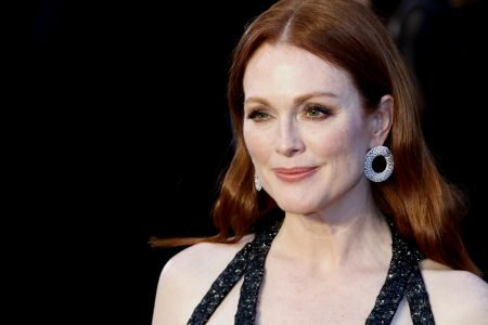 Julianne Moore smiles at a red carpet event. She is deep red hair that sits behind her shoulders, wears a strappy black dress and circular earrings.