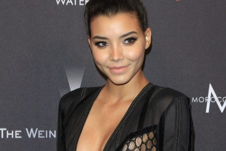 Nickayla Rivera smiles at a red carpet event. She wears a black dress with a deep V and her hair is tied up in an elegant bun.