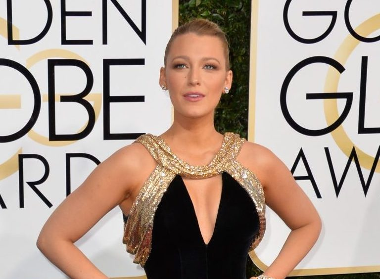 Blake Lively at the Golden Globes red carpet wearing a gold and black dress.