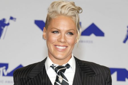 Pink smiles at a red carpet event. She has short blonde hair and wears a black suit and striped tie with a white shirt.