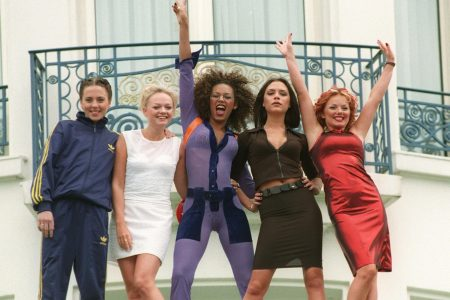The Spice Girls wave from a balcony.