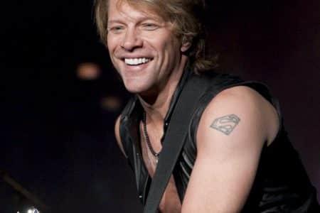 Jon Bon Jovi performing on stage smiling.