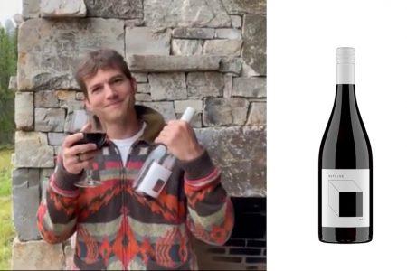 Ashton Kutcher holds up a bottle of his new Outside Wine.