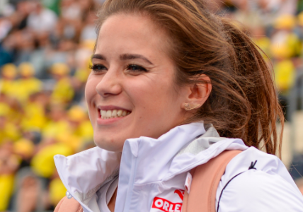 Maria Andrejczyk smiles at an athletic event wearing a Polish team jacket.