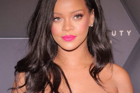 Rihanna at a red carpet event. She wears a strapless, bright pink dress and matching lipstick.