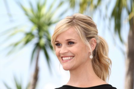 Reese Witherspoon smiles at an outdoor press event. She has blonde hair tie back in a loose ponytail.