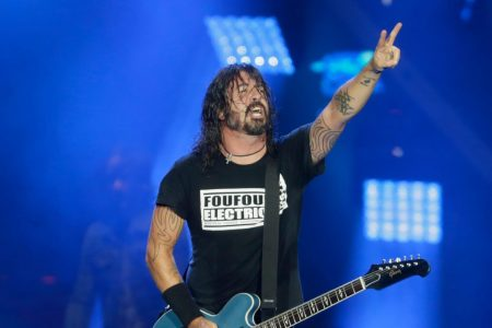 Dave Grohl performs on stage with one hand in the air making a peace sign.