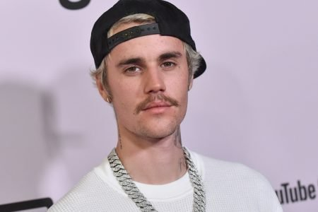 Justin Bieber at a red carpet event wearing a black cap, backwards, a white tee and a thick silver chain.