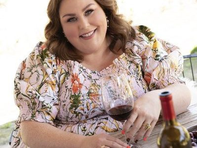 Chrissy Metz smiles, wearing a floral dress and setting at a table with a glass of wine.