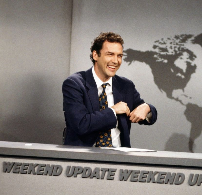 Norm Macdonald on the set of Saturday Night Live. He wears a suit and sits at the weekend news update desk.