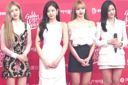 Blackpink members smile at a red carpet event.